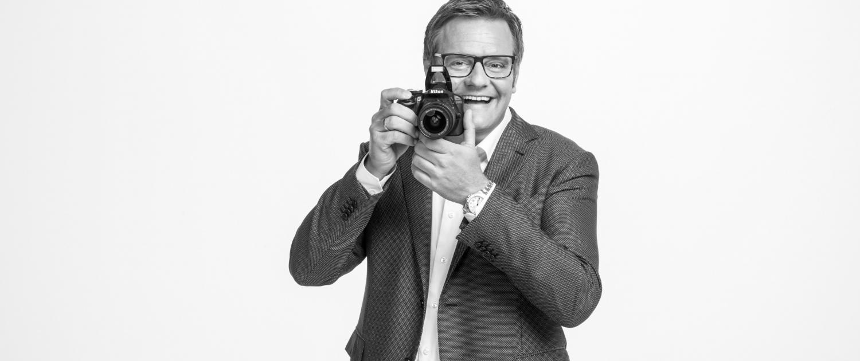 Robert hält eine Kamera vors Gesicht und lacht